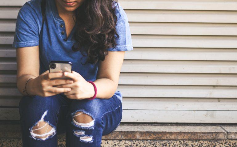 woman sitting at wall looking at phone