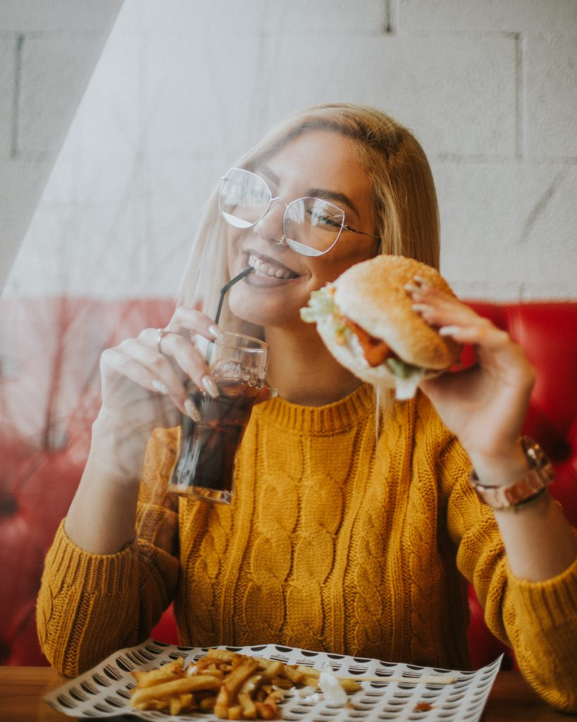 happy woman eating a burger